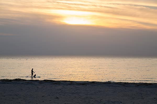 Fifth Avenue Beach paddleboarding into the sunset